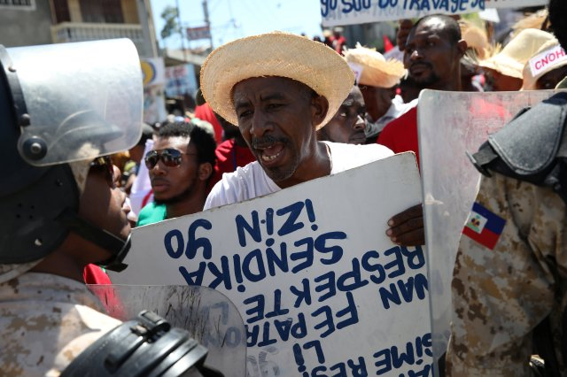 A man argues with a Haitian National Police officer March 1 as a police line blocks a street during a march for better labor conditions in Port-au-Prince. Life for Haitians has not appreciably improved since a devastating 2010 earthquake. (CNS/Reuters)