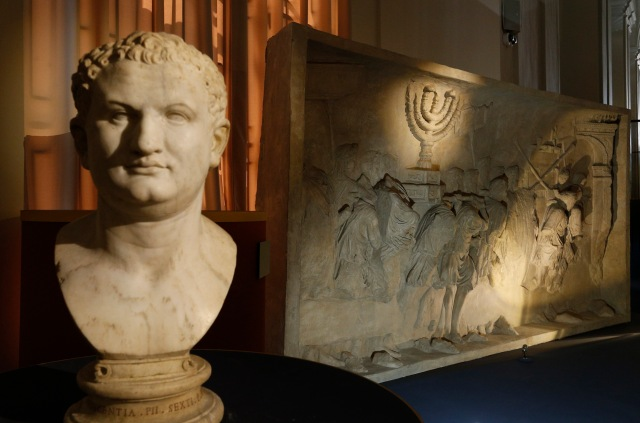A bust of Roman Emperor Titus is pictured next to a replica of the 1st-century Arch of Titus, showing Roman soldiers carrying the menorah, in a exhibition at the Vatican May 15. The replica of the Arch of Titus is the central motif in a two-part exhibition on the menorah at the Vatican and at the Jewish Museum in Rome. (CNS/Paul Haring)