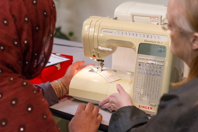 A volunteer works with a refugee from Afghanistan to help her learn how to use a sewing machine during a training session at a Catholic Charities program in Fredericksburg, Va. (CNS/Ashleigh Buyers, Catholic Herald)