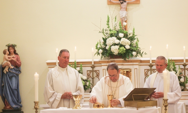 Bishop Robert E. Guglielmone of Charleston, S.C., center, concelebrates a 100th anniversary Mass at St. Francis of Assisi Mission in Walhalla, S.C., with Fathers Gregory West and William Hearne. (CNS/Christina Lee Knauss, The Catholic Miscellany)