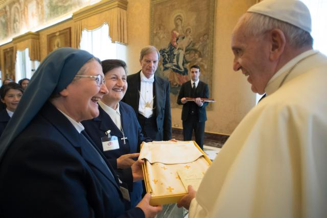 Pope Francis accepts a gift as he greets participants in the general chapter of the Sister Disciples of the Divine Master during an audience at the Vatican May 22. (CNS/L'Osservatore Romano)