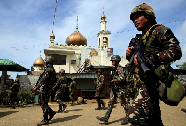 Philippine government soldiers walk past a mosque before their May 25 assault on Maute insurgents, who have taken over large parts of the town of Marawi. Residents started to evacuate Marawi after President Rodrigo Duterte imposed martial law across the entire Muslim-majority region of Mindanao. (CNS/Reuters)