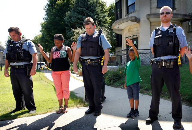 Parents and schoolchildren in Chicago pray over members of the city's police department during a barbecue in 2016 at the Academy of St. Benedict the African. The school held the event to thank local police for their support during the school year. (CNS/Karen Callaway, Chicago Catholic)