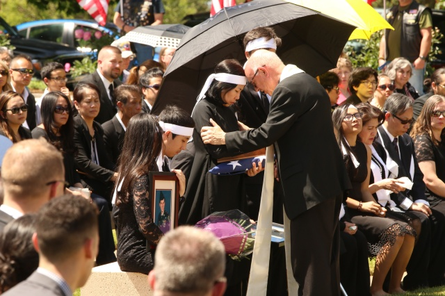 Msgr. Richard Paperini comforts Myhanh Best, wife of Ricky Best, who was killed on a Portland, Ore., commuter train May 26 while defending two girls from an anti-Muslim racist  attack. (CNS/Ed Langlois, Catholic Sentinel)