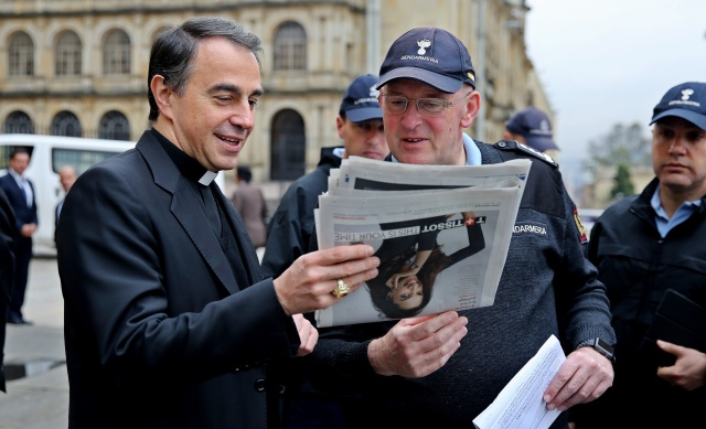 Archbishop Ettore Balestrero, apostolic nuncio to Colombia, and Domenico Giani, Pope Francis' lead bodyguard, look at a newspaper during a May 8 walk through the streets in downtown Bogota. The pope is scheduled to visit four Colombian cities in September. (CNS/EPA)