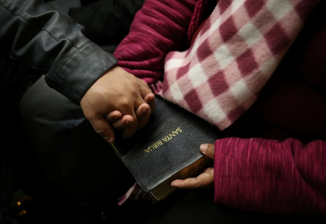 A couple in Toronto hold a Bible while commuting to a Spanish language Mass April 8. (CNS/Reuters)
