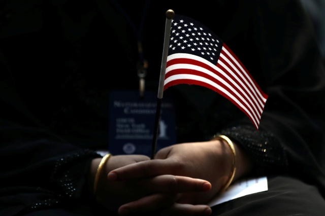 An immigrant holds a U.S. flag during a naturalization ceremony in New York City June 30. (CNS/Reuters)
