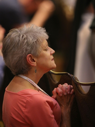 "A delegate prays during the closing Mass July 4 at the ""Convocation of Catholic Leaders: The Joy of the Gospel in America"" in Orlando, Fla. (CNS/Bob Roller)"