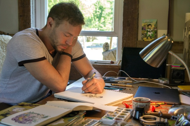 "Catholic cartoonist Ben Hatke sketches his character ""Zita the Spacegirl"" in a studio in his Front Royal, Va., home. His graphic novel series features a character who was named in honor of St. Zita. (CNS/Ashleigh Kassock, Catholic Herald)"