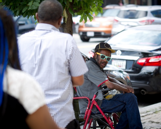 A man in Washington watches Holy Name of Jesus parishioner Eric Von Gay Sr., approach him with a lunch bag. More than 50 meals were distributed that day. (CNS/Jose Montoya)
