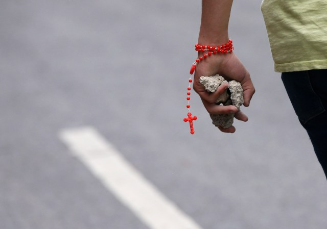 A demonstrator wears a rosary while holding chunks of concrete in Caracas, Venezuela, after clashes broke out July 30 during an election for the Constituent Assembly. (CNS/Reuters)