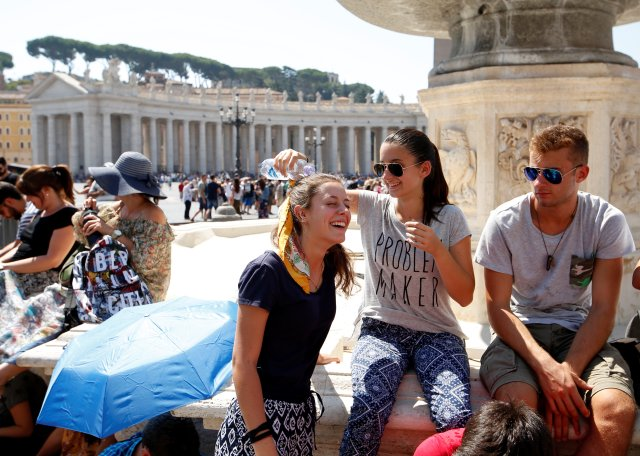 A girl refreshes a friend with a bottle of water as they wait for Pope Francis to lead the Angelus in St. Peter's Square Aug. 6 at the Vatican. (CNS/Reuters)