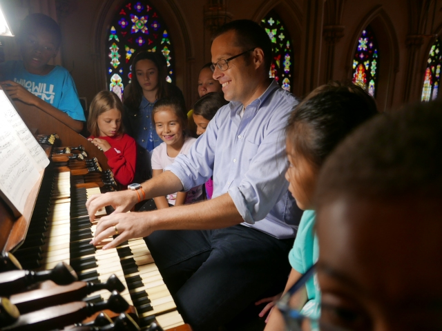 """Jared Lamenzo, organist at the Basilica of St. Patrick's Old Cathedral in the Manhattan borough of New York, plays the parish's 1868 Henry Erben Pipe Organ for an audience of appreciative youngsters July 26 during the parish's five-day music camp, aptly titled """"Pipes, Pedals & Peals."""" (CNS/Chris Sheridan)"""