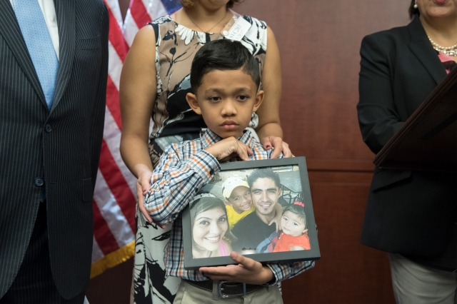 Seven-year-old Walter Escobar of Texas holds a photo of his family, including his deported father, Jose Escobar, during a late March news conference in Washington. Experts say law-abiding migrants are at greater risk of deportation under President Donald Trump. (CNS/EPA)
