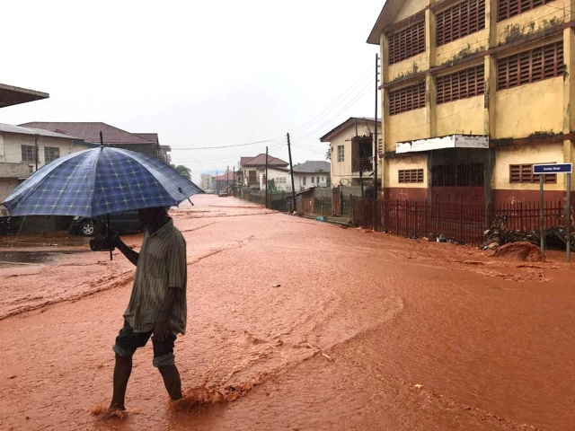A man walks in a flooded street in Freetown, Sierra Leone, Aug. 14. (CNS/DawnCharris, Instagram via Reuters)
