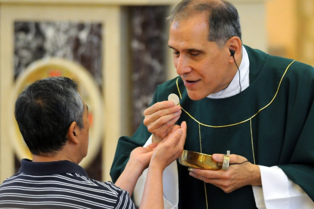 Father Bernard J. Ezaki, parochial vicar at St. Jane Frances de Chantal Church in Easton, Pa., gives Communion at Mass July 2. He has been legally blind since birth. (CNS/Ed Koskey Jr.)