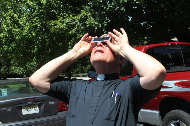 Father Richard Meredith, pastor of Sts. Peter and Paul Parish in Hopkinsville, Ky., catches the partial phase of the total solar eclipse on parish grounds Aug. 21. The town was near the point of maximum eclipse. (CNS/Dennis Sadowski)
