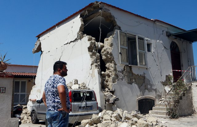 A man stands in front of a damaged house Aug. 22 after an earthquake hit Ischia, Italy. (CNS/Reuters)