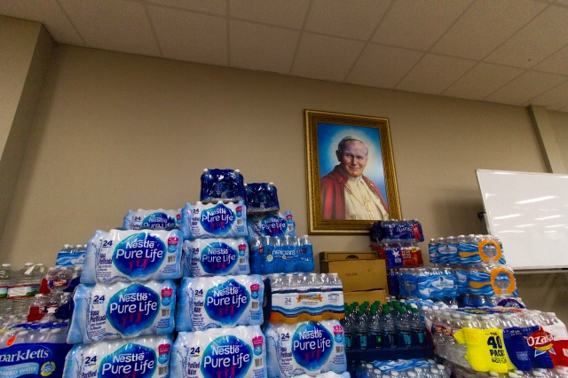 Cases of bottled water surround an image of St. John Paul II at an evacuee shelter Aug. 28 for people displaced by Tropical Storm Harvey at Sacred Heart Catholic Church in Conroe, Texas. The north Houston parish opened its doors when the massive storm crippled the Galveston-Houston region with continuous rains, causing rivers to overflow and prompting mandatory evacuations. (CNS/James Ramos, Texas Catholic Herald)