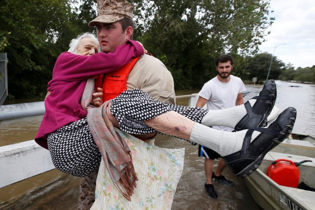 A worker helps an elderly woman from a rescue boat as it evacuates people from the floodwaters of Tropical Storm Harvey Aug. 30 in Houston. (CNS/Reuters)