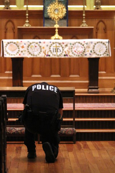 A police officer kneels in eucharistic adoration at St. Peter Catholic Church in Charlotte, N.C., in 2015. (CNS/SueAnn Howell, Catholic News Herald)