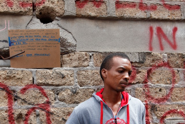 Josef, who said he arrived from Sudan 10 days earlier, holds clothes he received from volunteers as he stands on a street in Rome in 2016. In the background is a quote from Pope Francis about helping refugees. (CNS/Paul Haring)