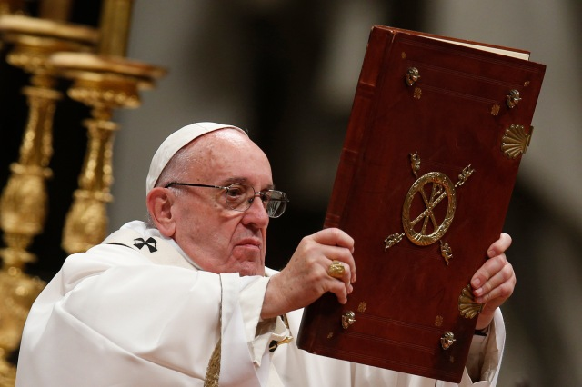 Pope Francis raises the Book of the Gospels as he celebrates Christmas Eve Mass in Peter's Basilica at the Vatican last year. (CNS/Paul Haring)