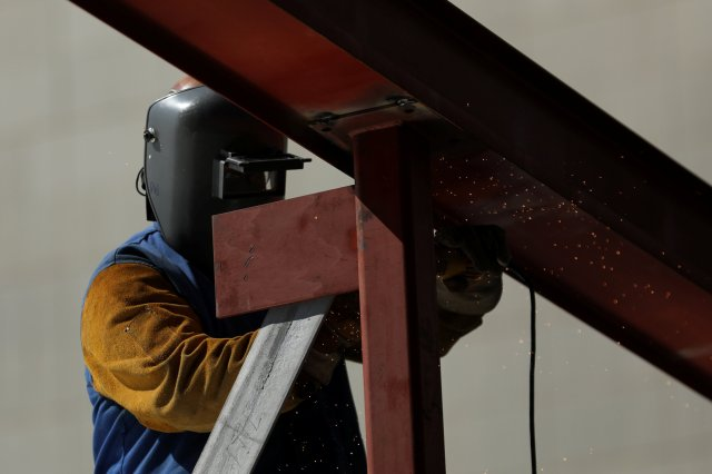 A worker uses a grinder on a metal beam Aug. 10 at a construction site in Los Angeles. Labor Day, honoring U.S. workers, is observed Sept. 4 this year. (CNS/Reuters)