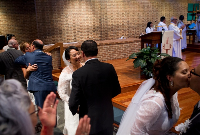 Maria and Arturo Perez kiss during their convalidation ceremony at Good Shepherd Catholic Church in Alexandria, Va. They joined other couples blessing their civil unions. (CNS/Tyler Orsburn)
