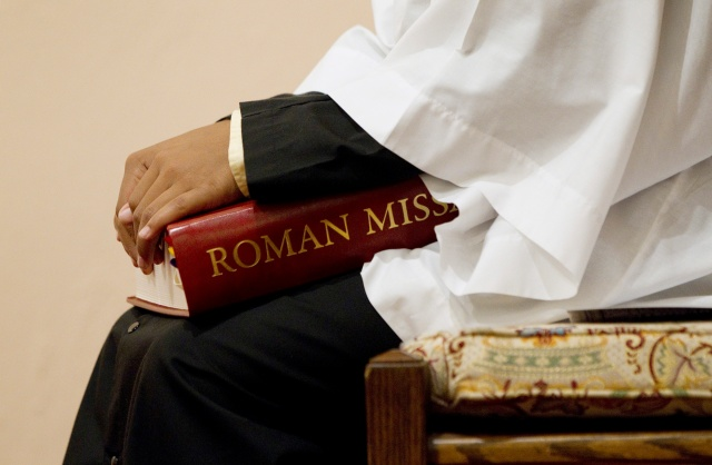 An altar server holds a copy of a Roman Missal during Mass. (CNS file/Nancy Wiechec)