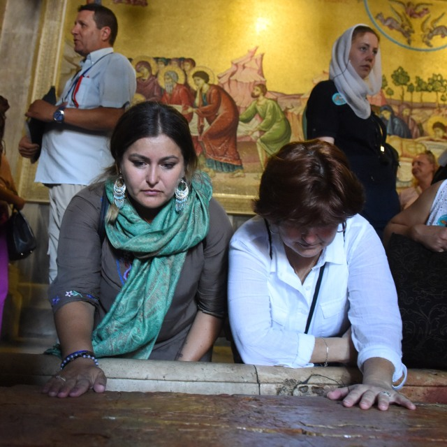 U.S. Army veteran Rocio Villanueva, 31, from Escondido, Calif., and U.S. Marine veteran Donna Perdue, 51, from Valparaiso, Ind., pray at the Stone of Unction in the Church of the Holy Sepulcher in the Old City of Jerusalem while touring the Holy Land with the Heroes to Heroes program Sept. 11. (CNS/Debbie Hill)