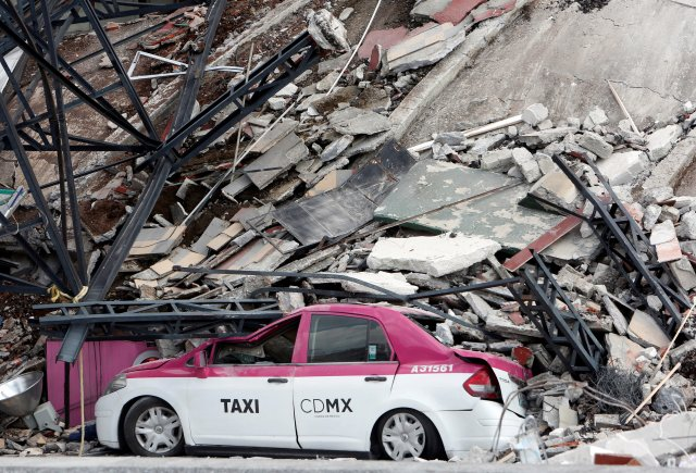 A damaged taxi is seen next to a collapsed building after the Sept. 19 earthquake in Mexico City. The magnitude 7.1 quake hit to the southeast of the city, killing hundreds. (CNS/Reuters)