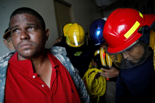 Rescue workers pray before walking out from the Emergency Operation Center in Guayama, Puerto Rico, after Hurricane Maria hit Sept. 20. (CNS/Reuters)