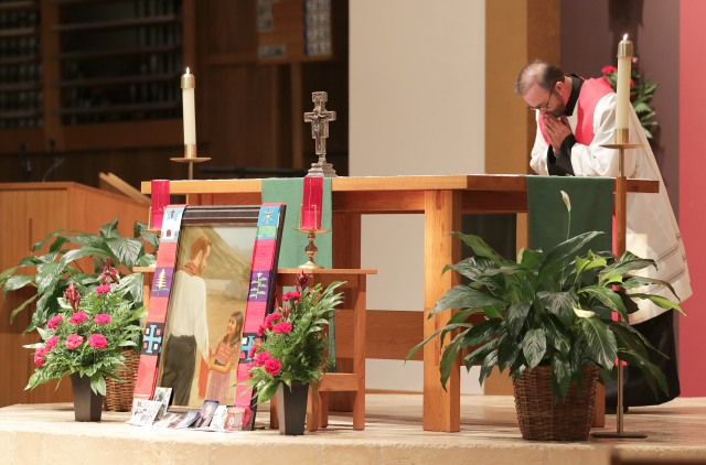 Father Joe Townsend, pastor of St. Benedict Parish in Broken Arrow, Okla., bows before the altar and an image of Father Stanley Rother during a Sept. 22 vespers and vigil. Father Rother, a priest of the Oklahoma City Archdiocese who was murdered in 1981 in the Guatemalan village where he ministered, was beautified the next day in Oklahoma City. (CNS/Dave Crenshaw, Eastern Oklahoma Catholic)