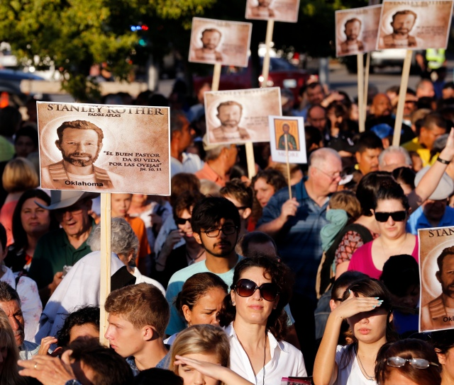 People hold placards with an image of Blessed Stanley Rother ahead of his Sept. 23 beatification Mass outside Oklahoma City's Cox Convention Center. (CNS/Steve Sisney, Archdiocese of Oklahoma City)