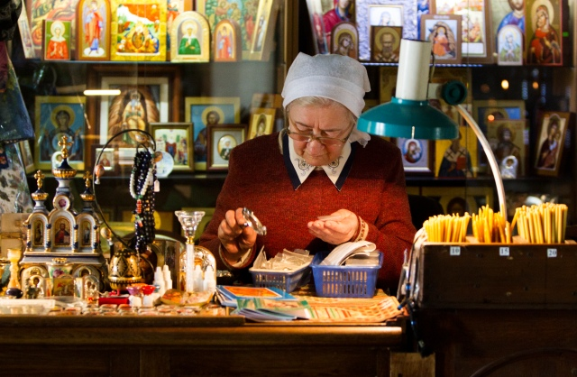 A clerk examines religious merchandise in the gift shop at the back of an Orthodox parish in Moscow. (CNS/Robert Duncan)