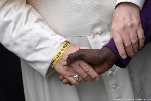 """Pope Francis clasps hands with a person at the """"Regional Hub,"""" a government-run processing center for migrants, refugees and asylum seekers, in Bologna, Italy, Oct 1. The pope is seen wearing a yellow ID bracelet with his name and a number, just like the immigrants and refugees at the center. (CNS/L'Osservatore Romano)"""