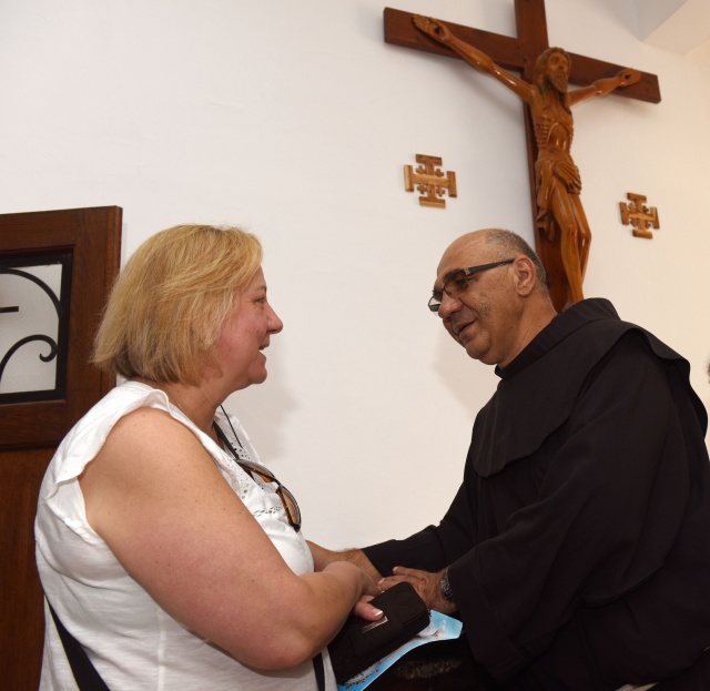 Franciscan Father Wladyslaw Brzezinski blesses Ursula Napierkowski of St. Paul's Parish in Kensington, Conn., inside the Church of the Visitation in Jerusalem. Father Brzezinski has been superior at the church for the past 10 years. (CNS/Debbie Hill)