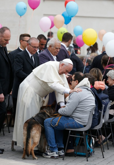 Pope Francis greets visually impaired people, accompanied by their dogs, during his general audience in St. Peter's Square at the Vatican Oct. 18. (CNS/Paul Haring)