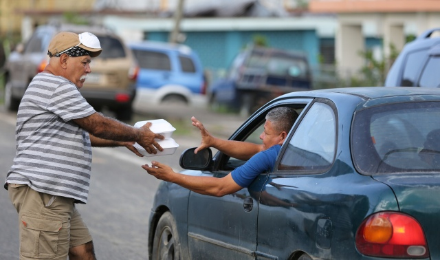 A volunteer hands food to a victim of Hurricane Maria Oct. 21 in Utuato, Puerto Rico. The town has been without power or water for more than a month after the hurricane devastated the island. (CNS/Bob Roller)