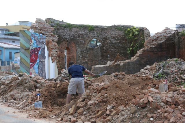 A man shovels dirt near a destroyed building Oct. 21 in Utuato, Puerto Rico. The town was devastated by Hurricane Maria and has been without water or power for more than a month. (CNS/Bob Roller)