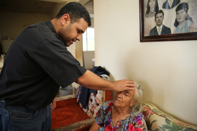 Father Carlos Francis Mendez, pastor of Immaculate Heart of Mary Church in Las Marias, Puerto Rico, blesses Luz Lamboy, 82, who has Alzheimer's and lives alone, at her home in a remote area outside the town Oct. 24. Father Mendez and parishioners distributed relief goods to her home and others who were affected by Hurricane Maria. (CNS/Bob Roller)