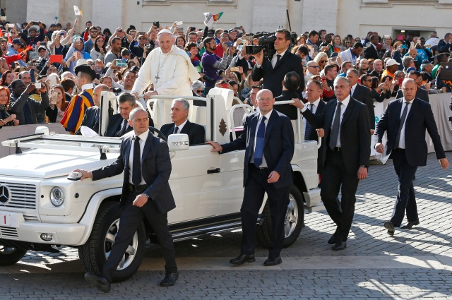 Vatican police officers in plainclothes walk alongside the popemobile during Pope Francis' general audience in St. Peter's Square at the Vatican May 3. (CNS/Paul Haring)