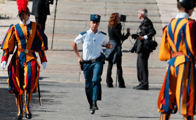 A Vatican police officer runs to his position as Pope Francis greets the crowd after a canonization Mass in St. Peter's Square at the Vatican Oct. 15. The Vatican police force was established 200 years ago, but its origins were in the fourth century. (CNS/Paul Haring)