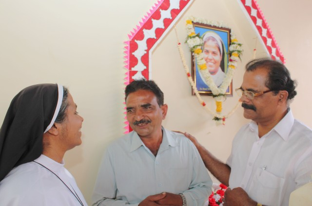 Samandar Singh, who killed Clarist Sister Rani Maria Vattalil Maria in 1995, is flanked by Clarist Sister Selmy Vattalil and Stephen Vattalil, elder brother of both the nuns, in 2015 at Sister Rani Maria's tomb in Udainagar, India. Sister Rani Maria will be beatified Nov. 4. (CNS/Anto Akkara)