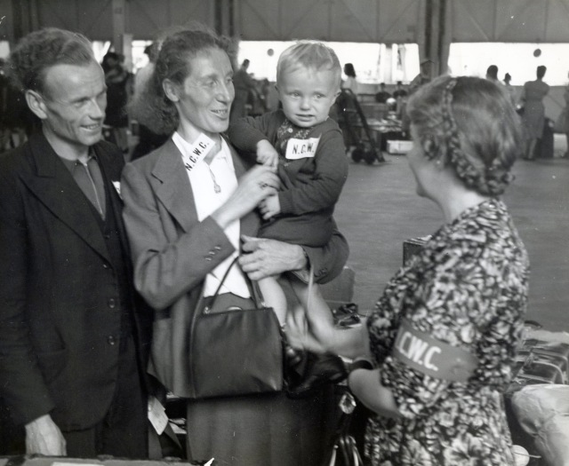 Refugees are greeted by a woman with the National Catholic Welfare Conference in 1957. The conference was the precursor to the U.S. Conference of Catholic Bishops. (CNS file photo)