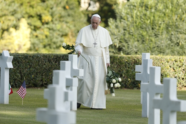 Pope Francis lays roses on graves at the Sicily-Rome American Cemetery and Memorial in Nettuno, Italy, Nov. 2. He commemorated all those who died in war by celebrating Mass at the cemetery, where thousands of American soldiers who were killed during World War II have their final resting place. (CNS/Paul Haring)