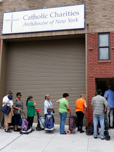 People wait to enter a food pantry at Catholic Charities of the Archdiocese of New York's community center in the South Bronx in 2016. The chairmen of three U.S. bishops' committees said the current draft of the House of Representatives tax reform bill raises income taxes on the working poor and gives a large tax cut to the wealthy. (CNS/Gregory A. Shemitz)