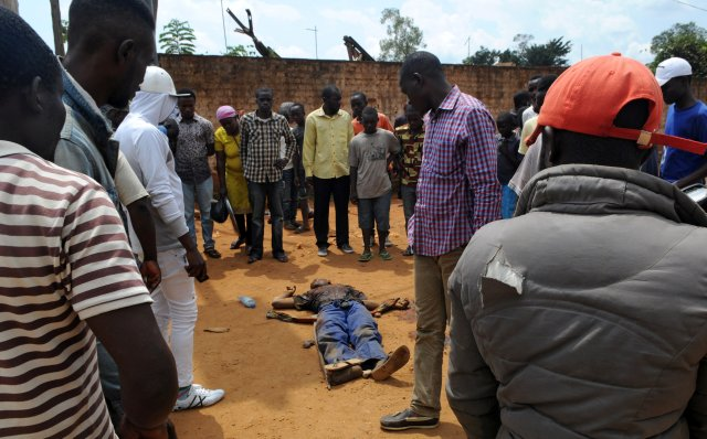 Civilians gather around the body of a man killed during fighting between the army and militia fighters in Beni, Congo, in late June. (CNS/Reuters)