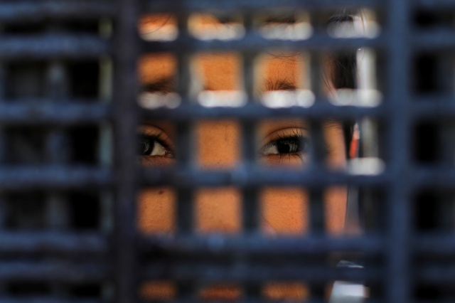 A boy in Mexico looks through the border fence at Border Field State Park in San Diego Nov. 18.  (CNS/Reuters)